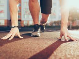 Muscoli, mani, luce solare, gambe in scarpe da ginnastica di un ragazzo forte allo stadio al mattino. Ha la preparazione in partenza